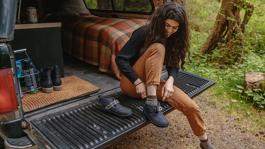 Woman putting on her Ramble booties while sitting on a truck bed gate