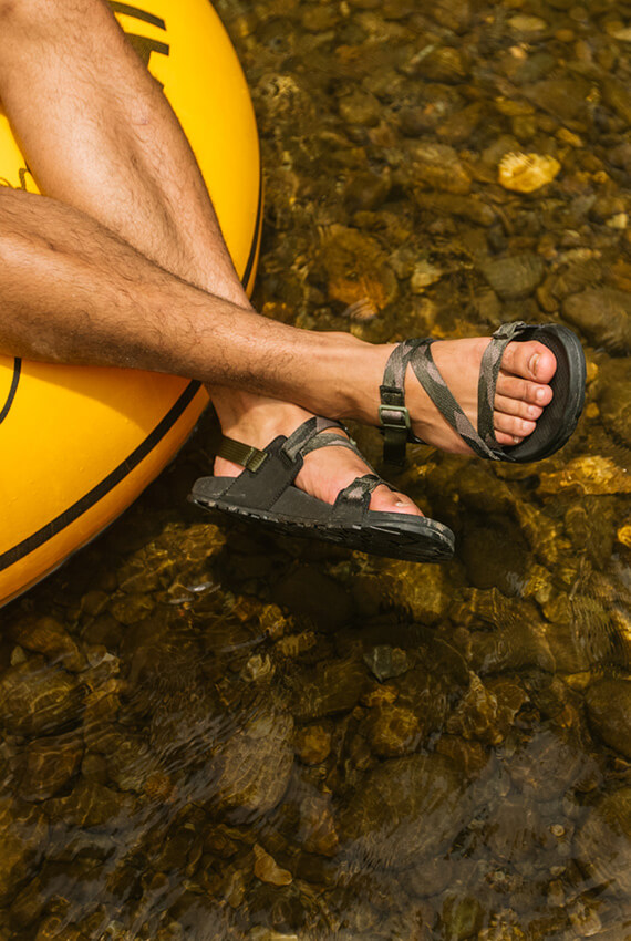 Chacos on feet dangling over a tube, floating down a shallow river.