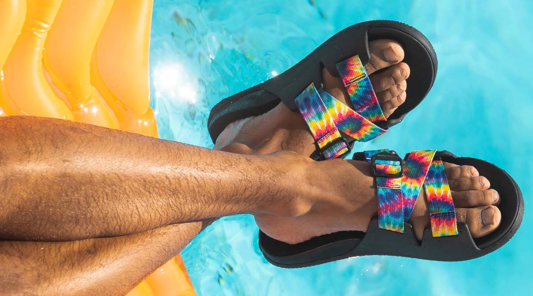 Person sporting rainbow chaco slides.