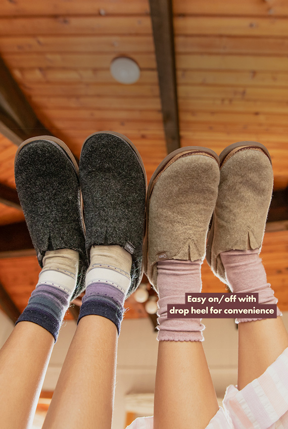 Two pairs of feet in the air wearing Revel shoes.