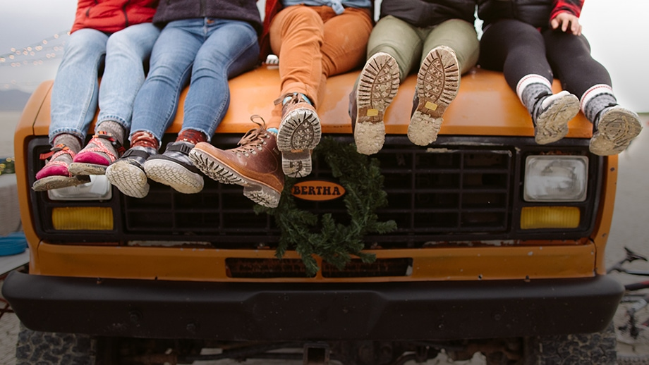5 People sitting on the hood of a truck, wearing various Chaco sandals, shoes and boots
