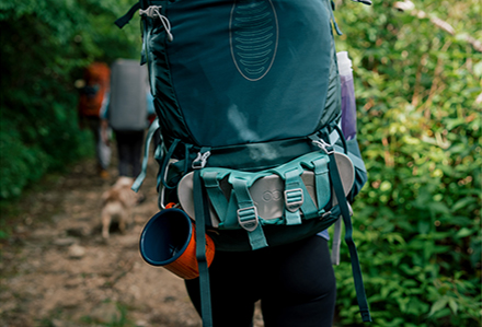 Close up of a backpack on a female's back, with a pair of Chaco Chillos strapped to the outside.