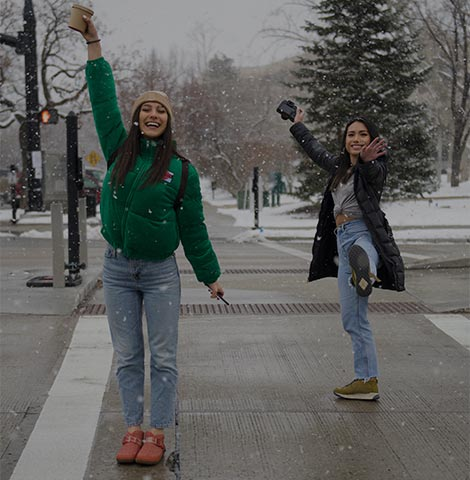 Two women holding up their coffe cups on a sidewalk in the snow.