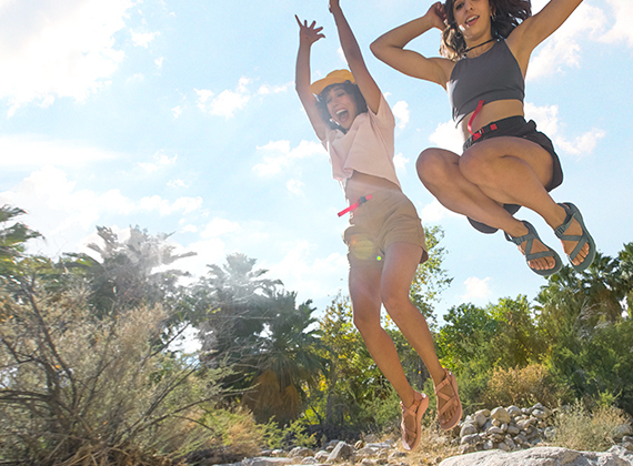 Two women jumping in the air on a sunny day with their Z Chromatic Sandals on.