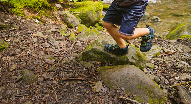Kid runs on top of rocks in the woods while wearing Odyssey sandals.