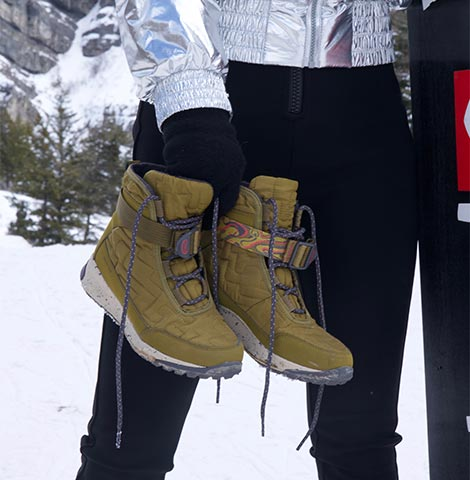 Woman walking in the snow and ice staying warm in her Borealis Quilt boots.