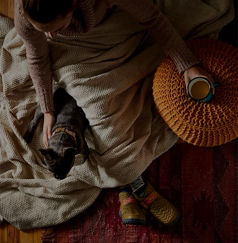 Woman getting warm with a blanket and her cat wearing a pair of Chaco boots.
