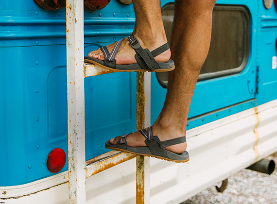 Man climbs up the ladder on the back of a blue and white bus while wearing Chaco sandals.