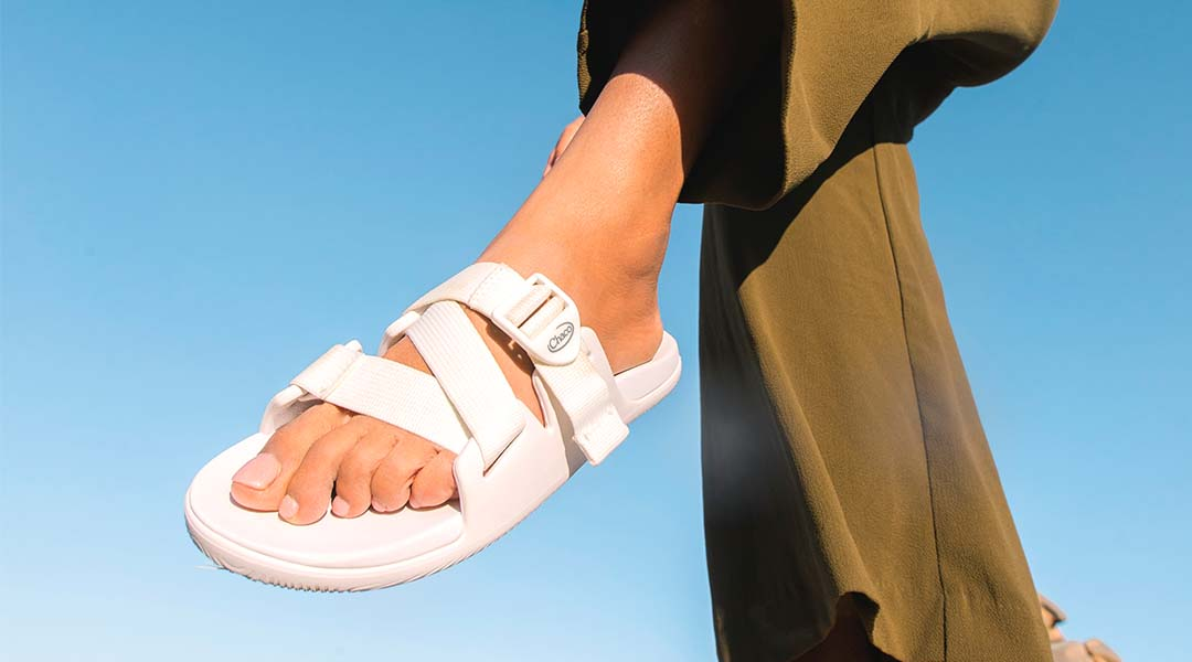 Person sporting white chaco slides.