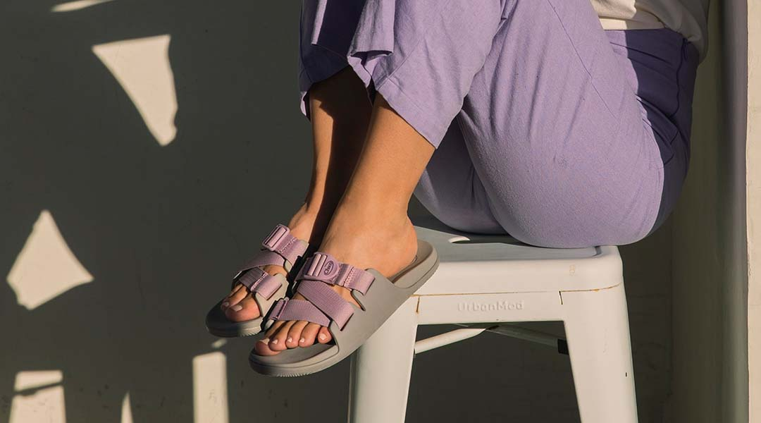 Person sitting ina chair, sporting grey chaco slides.