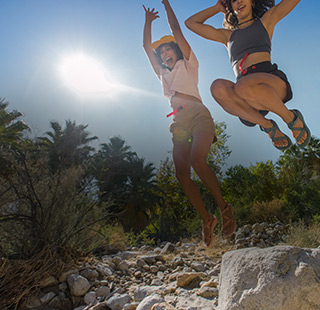 Two females jumping from rocks in the midday sun, with big smiles on their faces and Chaco sandals on their feet.