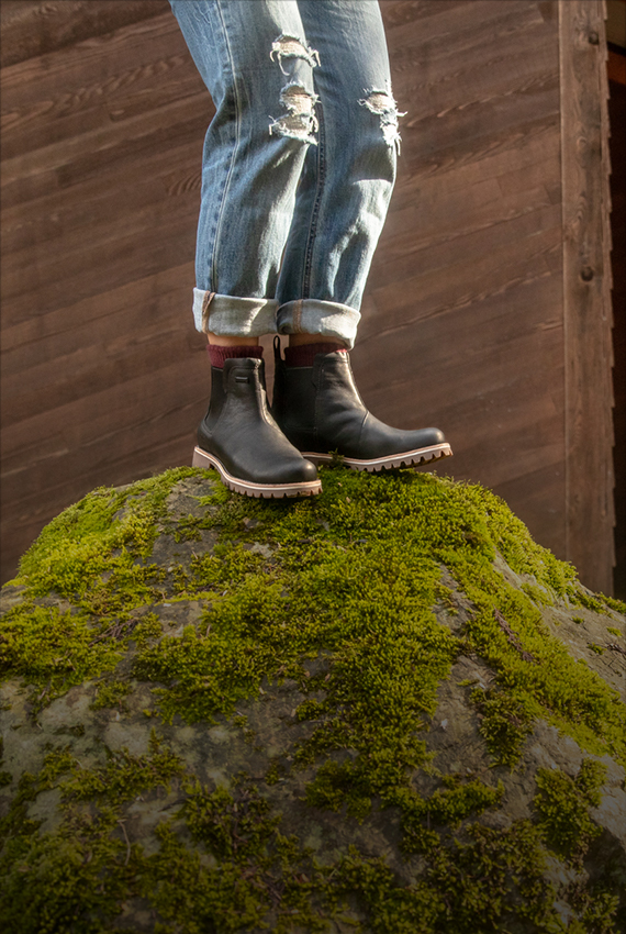 Woman standing precariously on a mossy rock but she stands assured in the grip of her Chaco Chelsea boots.