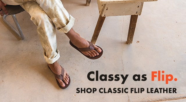 Person sitting in a chair, wearing Chaco classic flip flops.