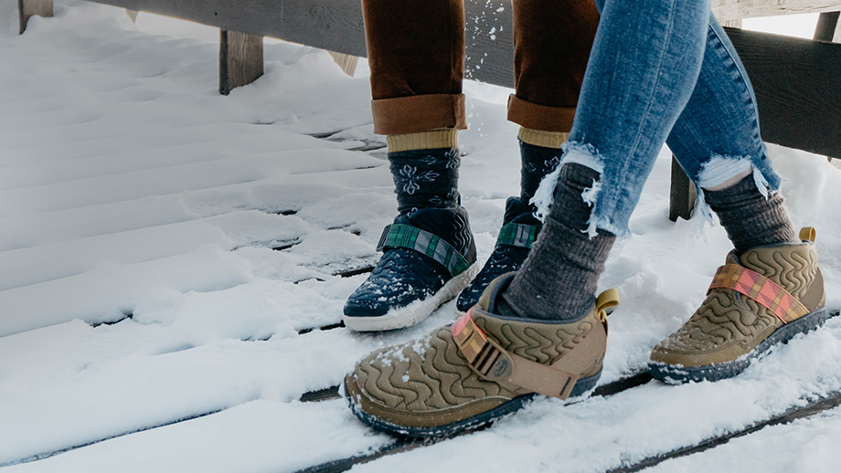 Two women sitting on a wooden bench with snow under their quilted Chaco Ramble boots.