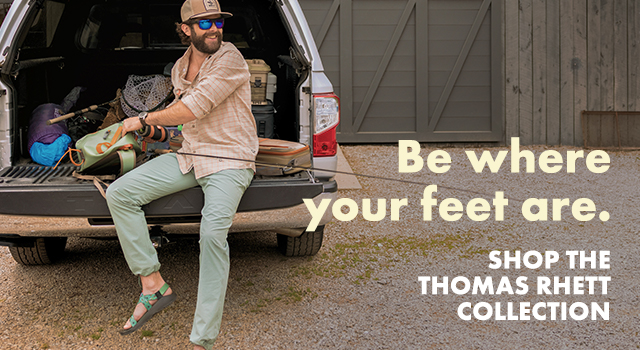 Thomas Rhett wearing his signature sandals in the truck of a car while getting a fishing pole set.