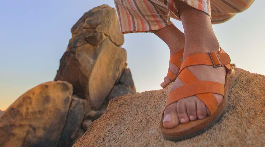 Person on a rock, sporting Chaco Women's Wayfarer sandals.