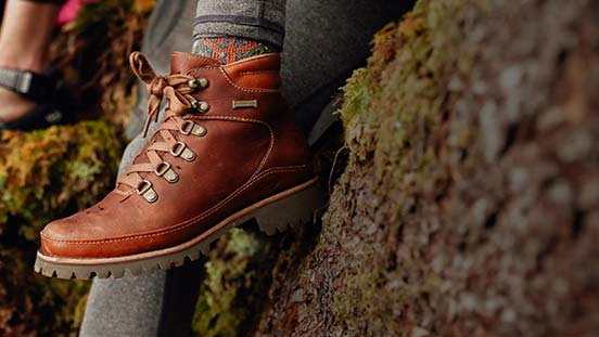 Brown waterproof Chaco boot on a women sitting on a mossy rock.