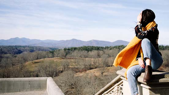 Woman looking out at the mountains with Chacos on.