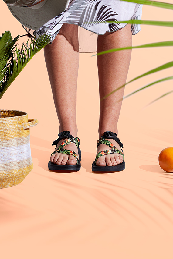 A pair of feet sneak out from a summery dress while wearing a pair of customized Chaco sandals with foliage on the straps.