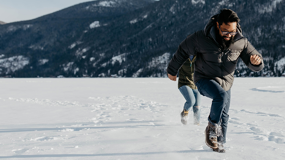 Man running in Chaco boots across a frozen lake.