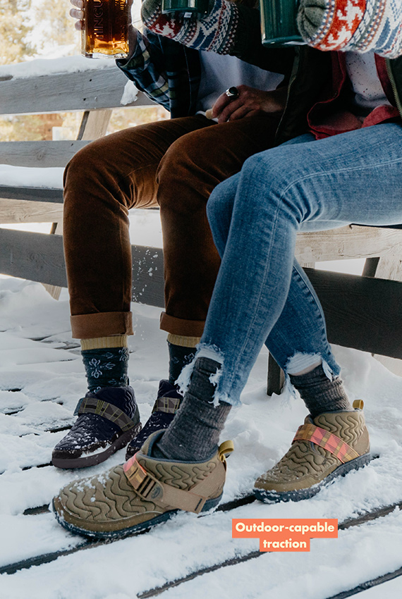 Two people sit on a bench with their feet in the snow wearing Ramble shoes.