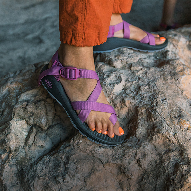 Person standing on a rock wearing Chaco sandals