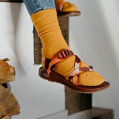 Person sitting on stairs wearing Chaco sandals and orange socks