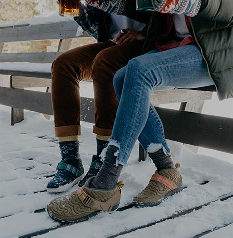 Two people sitting on a snow covered bench.