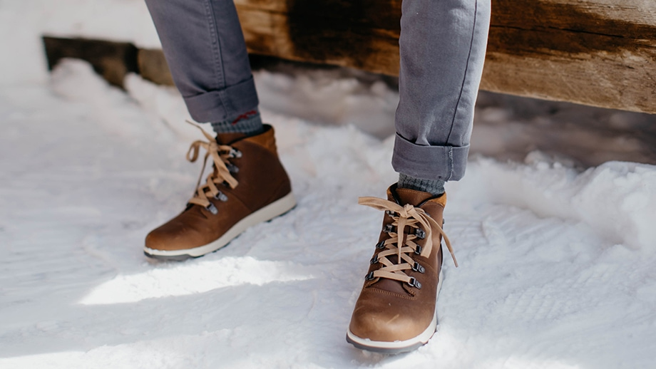 Person sitting on an outdoor bench in the snow, wearing brown Chaco boots