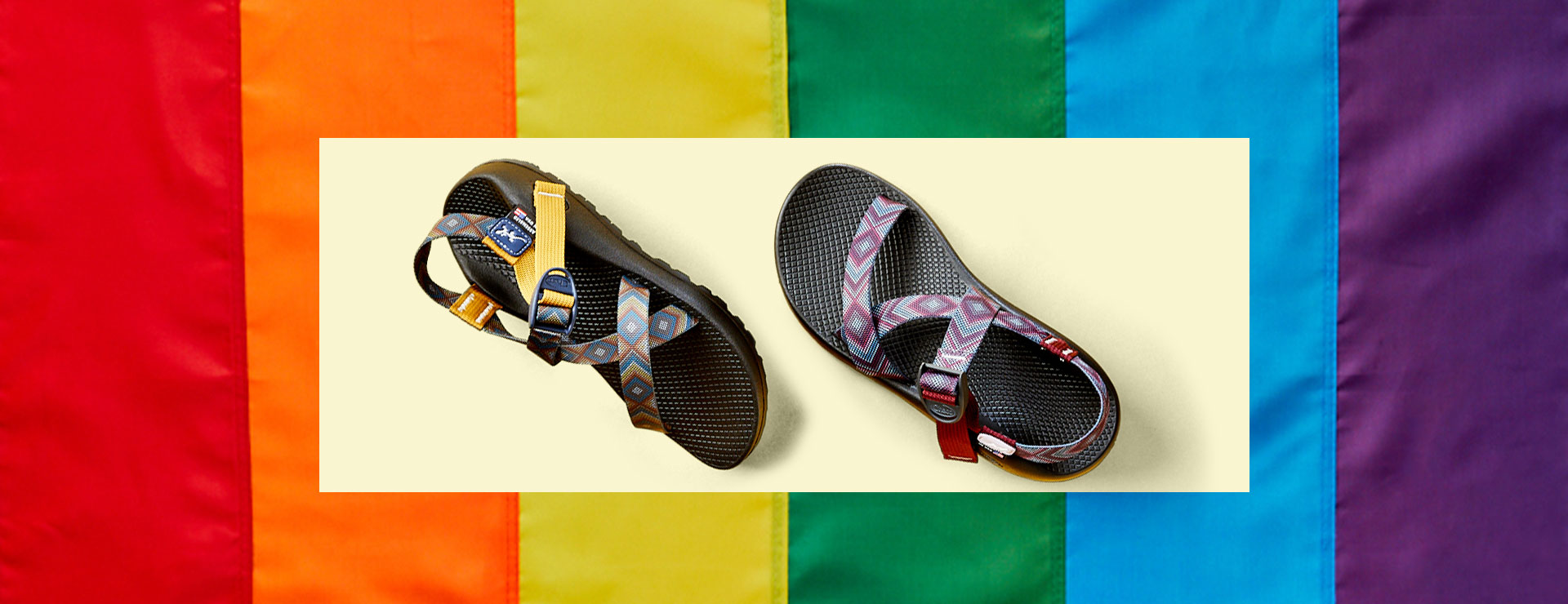 Several colorful styles of Chaco sandals over a rainbow flag.