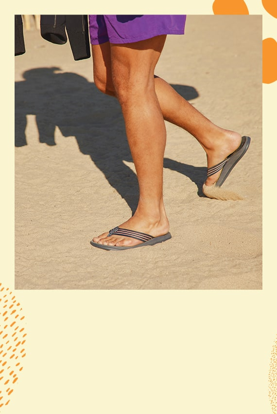 A person walking on the bearch, wearing Chillos Flips.
