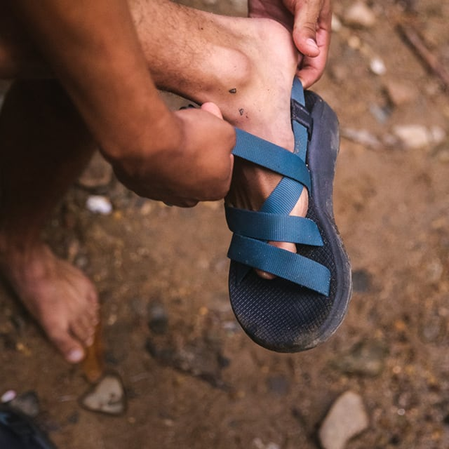 Person putting on a Chaco sandal outside