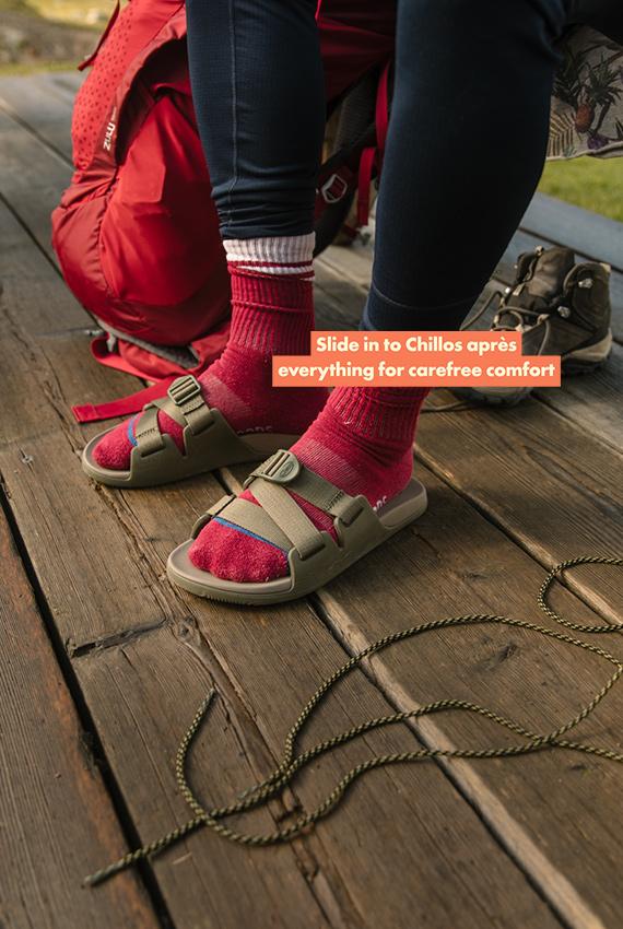 Feet in socks and Chillos on a boardwalk beside hiking gear.