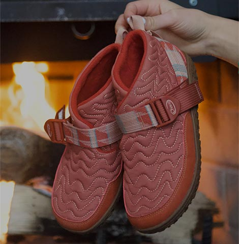 Holding up a pair of Brick colored Ramble Boots with a fireplace in the background.
