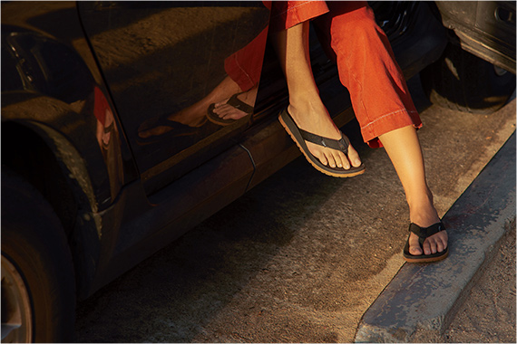 Stepping out of a car onto the curb in a pair of Lowdown flips.