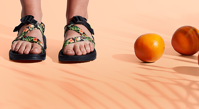 Woman standing amid oranges while wearing custom Chaco sandals with tropical designs on the bands.