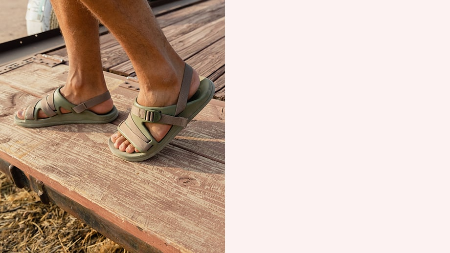 A man's feet wearing Chillos Sport sandals on a wood deck.