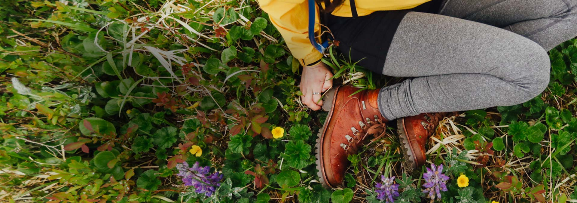Brown waterproof boots on a woman sitting in a field.