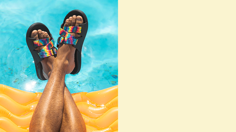 A man's feet wearing tie-dyed Chillos suspended over a pool.
