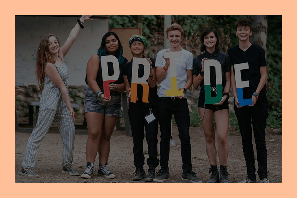 A group of young people stand in a line holding letters that spell out PRIDE.
