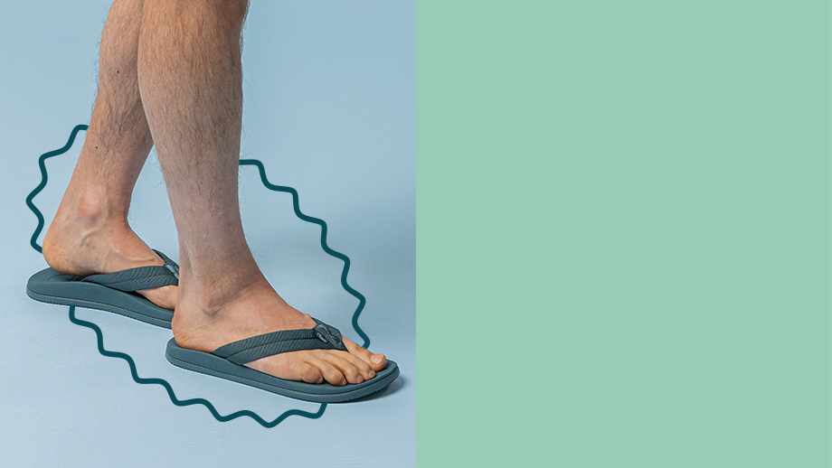 Man's feet wearing blue Chaco flip flops against a blue and green background.