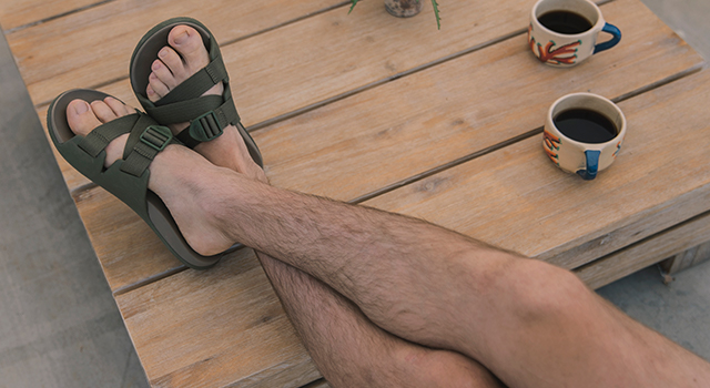 A man sits with legs crossed and feet up on table with cups of coffee and his Chillos slide sandals.