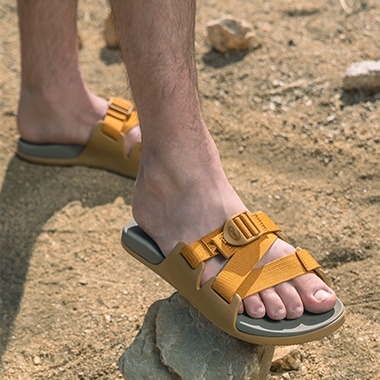 Man standing on the beach wearing Chaco Chillos sandals.