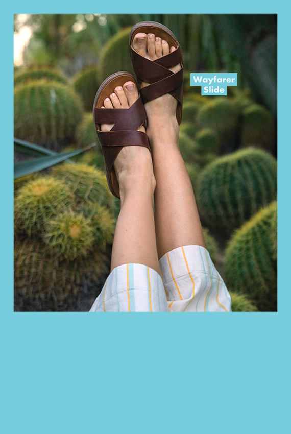 Feet elevated into the air in front of a field of cacti wearing wayferer slides.
